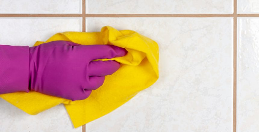 A gloved hand holds a rag and washes ceramic tiles